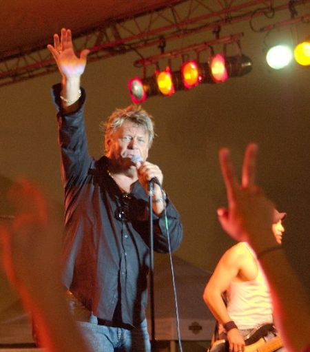 Brian Howe singing at a concert in a black shirt.