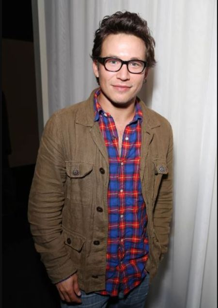 Actor Jonathan Taylor Thomas in a brown jacket poses for a picture.