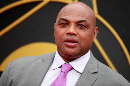 Charles Barkley in a grey suit poses at  a studio.