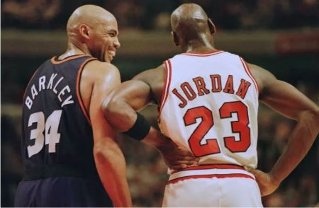 Barkley in black jersey laughs with Michael Jordan.