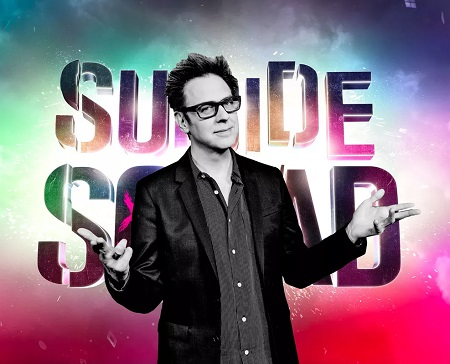 James Gunn in front of a 'Suicide Squad' poster.