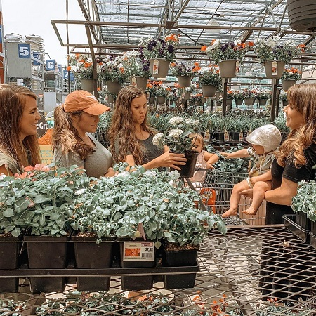 Anna Duggar carrying her youngest daughter in the flower nursery with her three Duggar sister-in-laws.