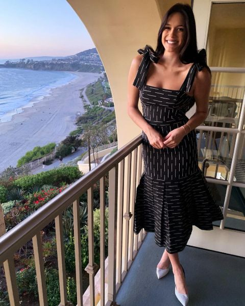 Audra Mari in a black dress poses a picture.