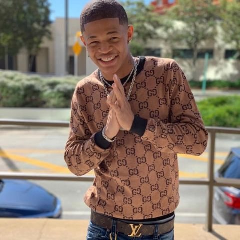 YK Osiris poses for a picture in a brown sweater.