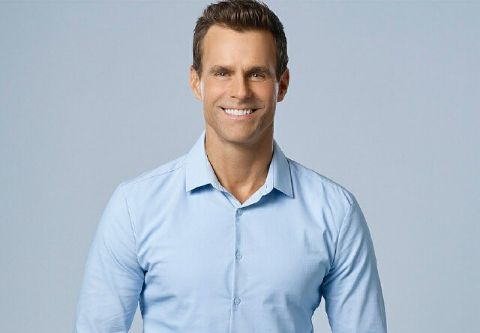 Cameron Mathison in a blue shirt poses for a picture.