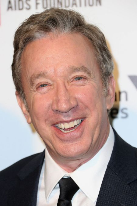 Tim Allen in a black suit poses for a picture.