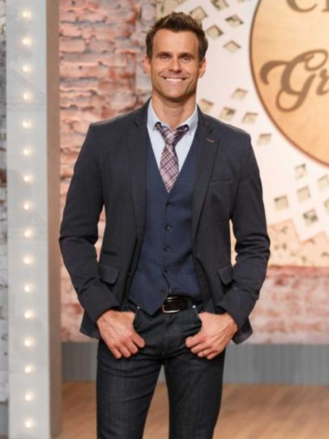 Cameron Mathison in a black suit poses for a picture.