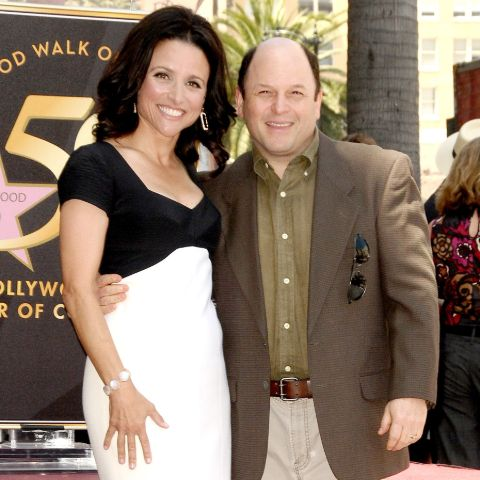Jason Alexander in a brown coat poses a picture with wife Title.