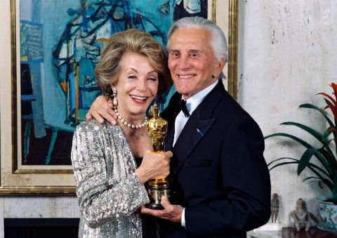 Anne Douglas and Kirk Douglas pose with an award.