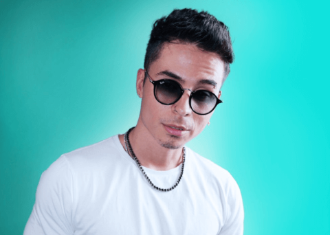 Reykon in a white t-shirt poses for a picture.