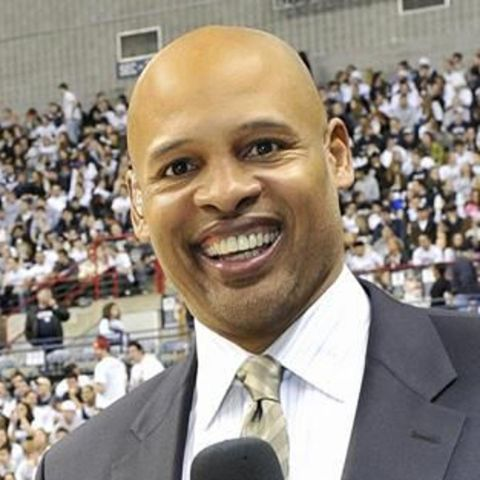 Clark Kellogg in a black suit poses a picture.